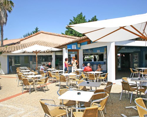 An outdoor fine dining restaurant with sunshades.
