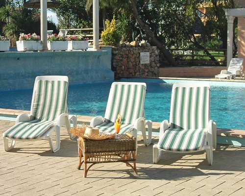 View of chaise lounge chairs alongside the swimming pool.