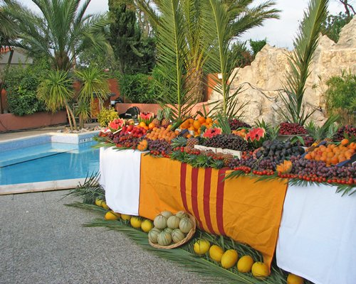 An outdoor buffet with fruits alongside the pool.