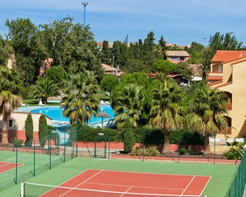 An outdoor tennis court alongside resort units surrounded by trees.