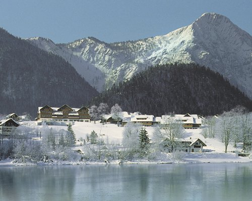 An exterior view of the resort units with pine trees and lake covered in snow.