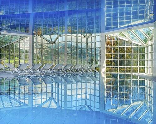 An indoor glass covered swimming pool with chaise lounge chairs and an outside view.