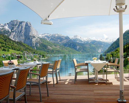 An outdoor dining with sunshade alongside the lake surrounded by mountains.