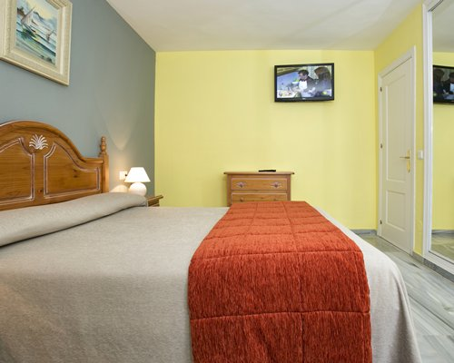 A well furnished bedroom with a double bed and television.