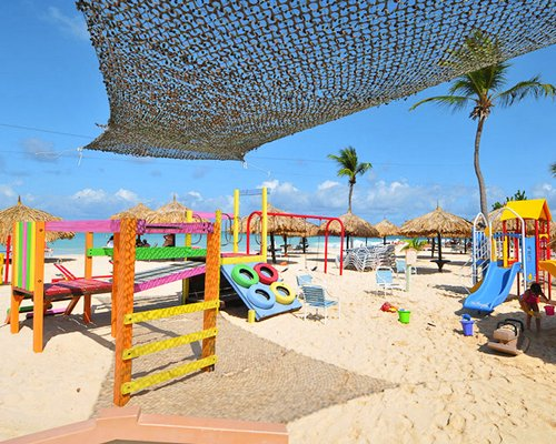 Kids playscape with palm trees and thatched sunshardes alongside the beach.