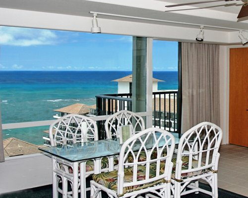 A glass top dining area with a balcony and beach view.