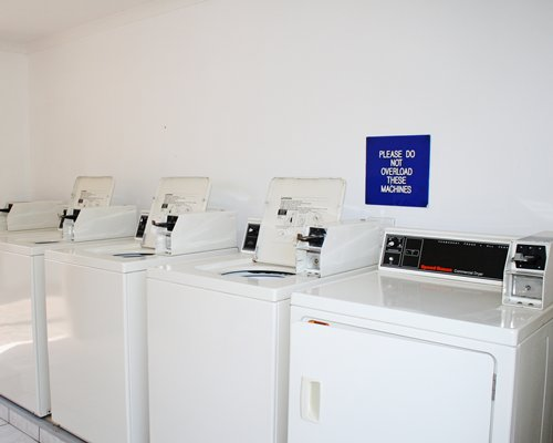An indoor laundry room with four washing machines.