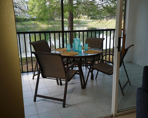 An outdoor dining area in the balcony with a lake view.