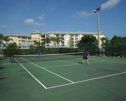 Outdoor tennis courts alongside resort units.