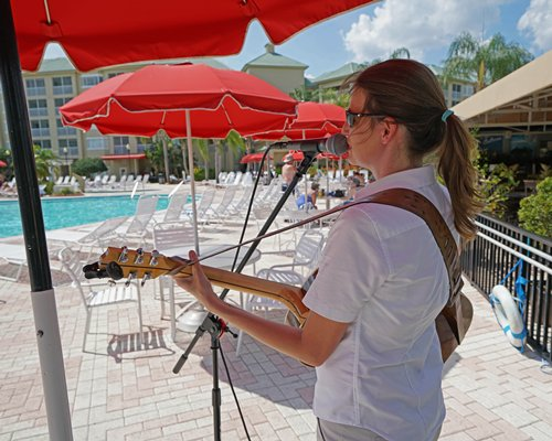A person playing violin alongside the swimming pool with chaise lounge chairs.