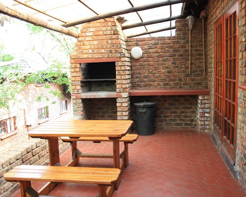 Outdoor picnic area with wooden bench and barbecue grill.