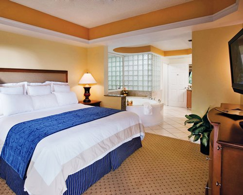 A well furnished bedroom with a king bed hot tub and television.