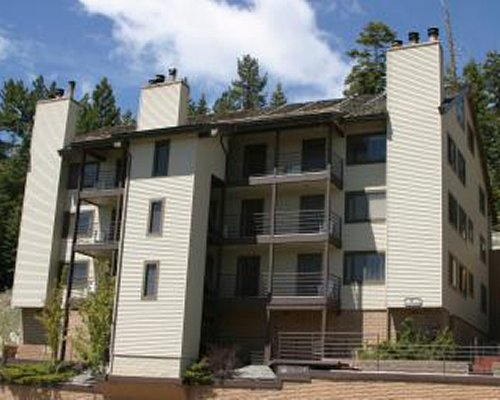 Exterior view of a unit with multiple balconies at GEOHoliday surrounded by wooded area.