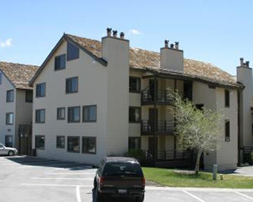 An exterior view of the resort unit with car parking lot.