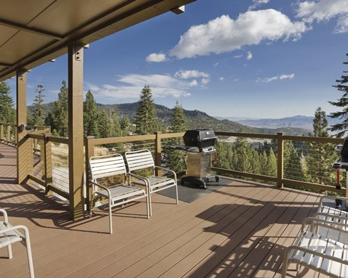 A balcony with barbecue grill and patio chairs alongside the trees and mountains.