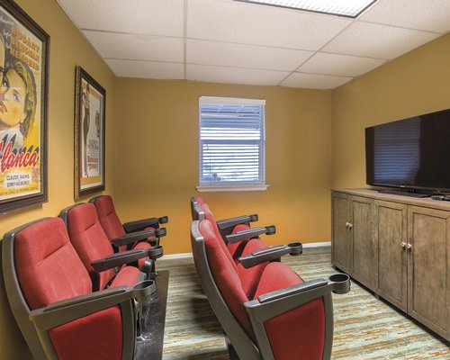 A well furnished mini theatre room with chairs.