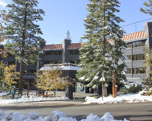 An exterior view of the Tahoe Seasons Resort covered in snow.