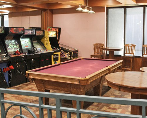 An indoor recreational area with a pool table and arcade.