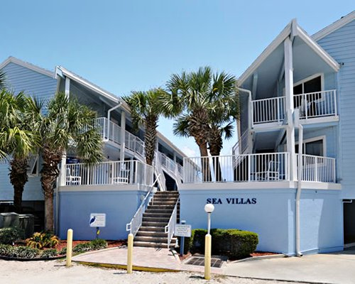 An exterior view of the Sea Villas At New Smyrna Waves By Exploria Resorts with palm trees.