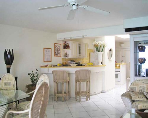 An open plan living and dining area alongside a kitchen with breakfast bar.