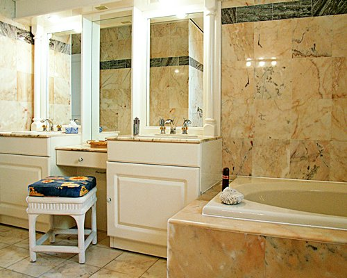A bathroom with a dresser and a bathtub.