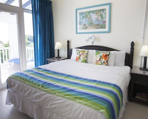 A well furnished bedroom with a king bed and outdoor patio.