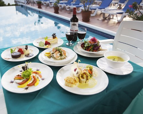 Various food placed on a table alongside a swimming pool with chaise lounge chairs.