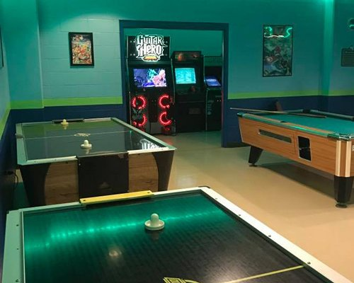 An indoor recreation room with pool table air hockey and arcade games.