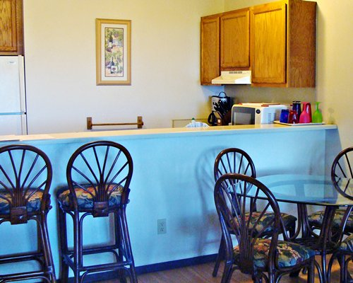 A well equipped kitchen with a dining table and breakfast bar.