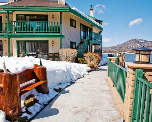 Exterior view of pathway to a unit with multiple balconies at Lagonita Lodge alongside a lake during winter.