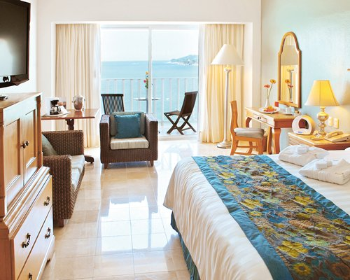 A well furnished bedroom with television dining area balcony and patio chairs with bay view.