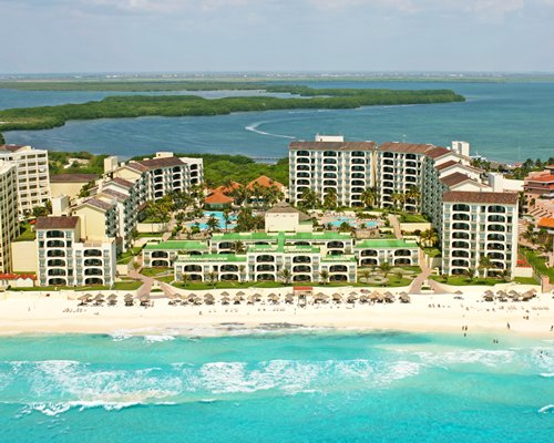 Exterior view of Royal Mayan alongside the beach surrounded by the ocean.