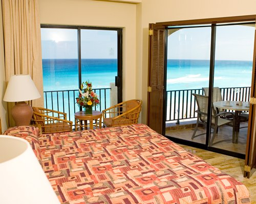 A well furnished bedroom with a beach view.