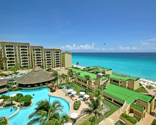 An aerial view of Royal Mayan with outdoor swimming pool alongside the ocean.