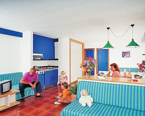 A family in an open plan living room and dining area with a television.