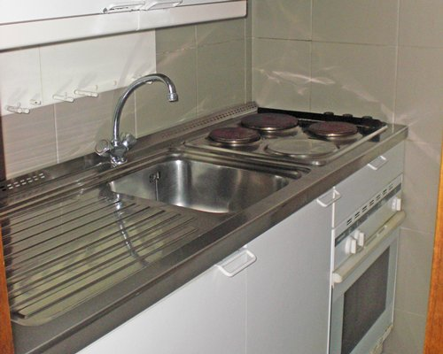A kitchen with stove and a sink.