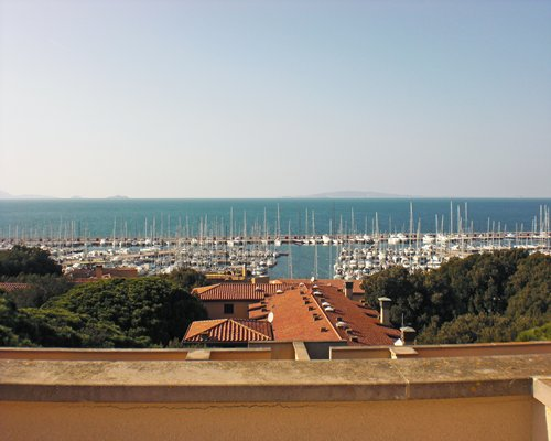 A balcony view of a marina alongside the ocean.
