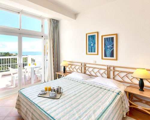 A well furnished bedroom alongside a balcony with patio furniture.