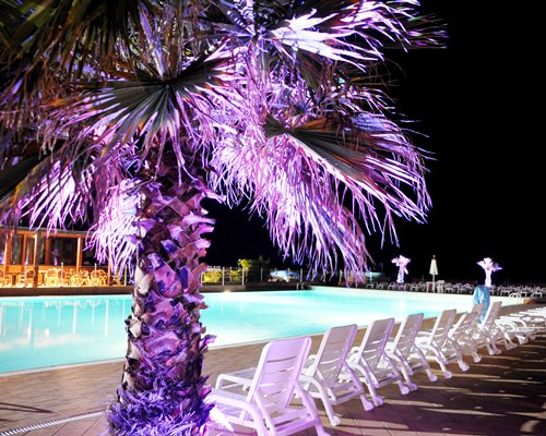 Large outdoor swimming pool with chaise lounge chairs at night.