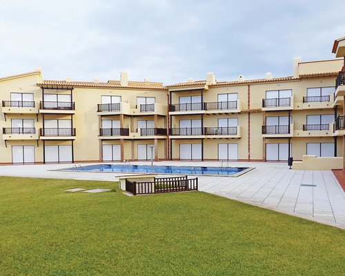 View of multiple unit balconies with an outdoor swimming pool.