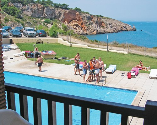 A balcony view of a swimming pool alongside the ocean.