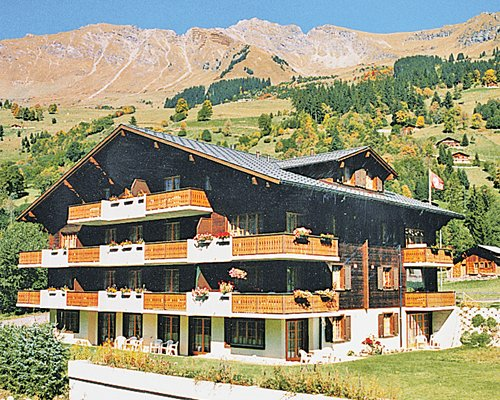 Exterior view of Residence Diablerets with multiple unit balconies with wooded area and mountains.