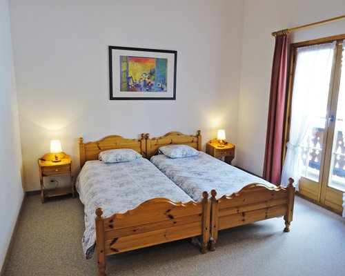 A well furnished bedroom with two twin beds and balcony.