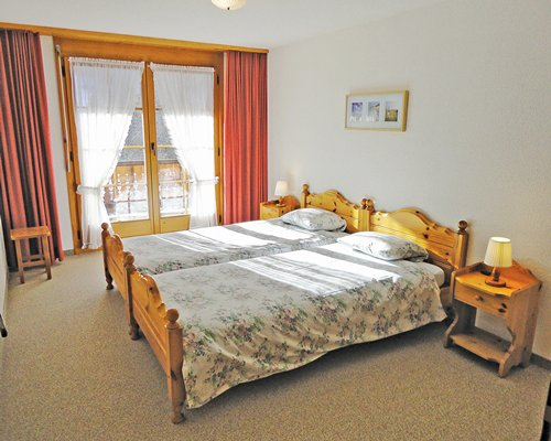 A well furnished bedroom with two twin beds and an outdoor view.
