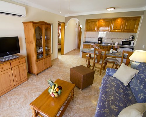 A well furnished living room with open plan kitchen dining area and television.