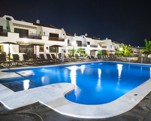 A large outdoor swimming pool with chaise lounge chairs alongside resort units.