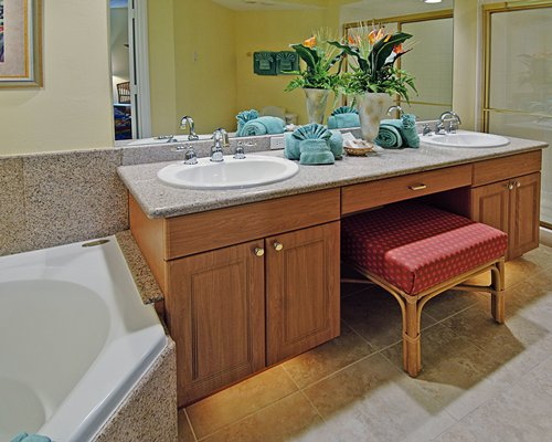 A bathroom with a bathtub and double sink vanity.