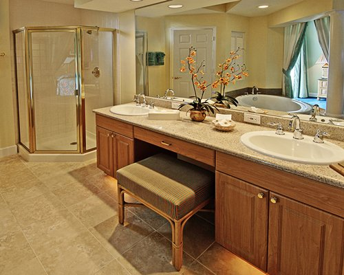 A bathroom with standing shower and double sink vanity.