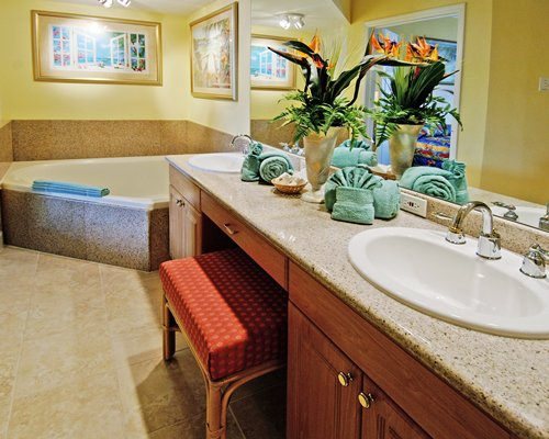 A bathroom with bathtub and a single sink vanity.
