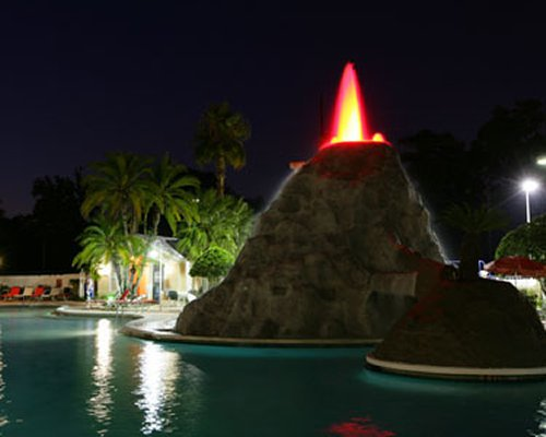 An outdoor swimming pool with fountain and chaise lounge chairs at night.